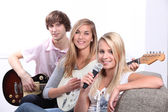 Three teenager playing musical instruments — Stock Photo