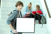 College student holding a black framed board left blank for your image — Stock Photo