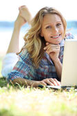 Vrouw met laptop buiten op een zonnige dag — Stockfoto