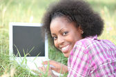 Woman using a laptop in the grass — Stock Photo