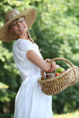 Young woman with a basket of fresh fruits — Stock Photo