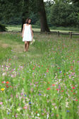 Summery woman walking through a pretty wild flower meadow — Stock Photo