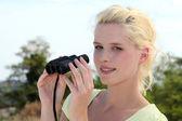 Woman holding binoculars — Stock Photo