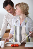 Couple in the kitchen with recipe book — Stock Photo