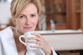 Blond woman in dressing gown drinking coffee — Stock Photo
