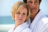 Couple at the beach wearing dressing gowns — Stock Photo