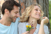 Husband offering wife flowers — Stock Photo