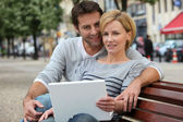 Couple on a bench with laptop — Stock Photo