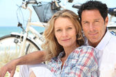 Happy couple sitting by the beach with their bikes — Stock Photo