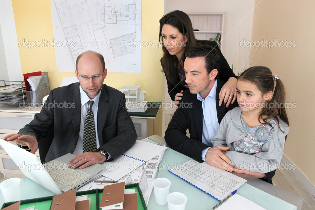 Family sitting in an architect's office  Stock Photo #7712826