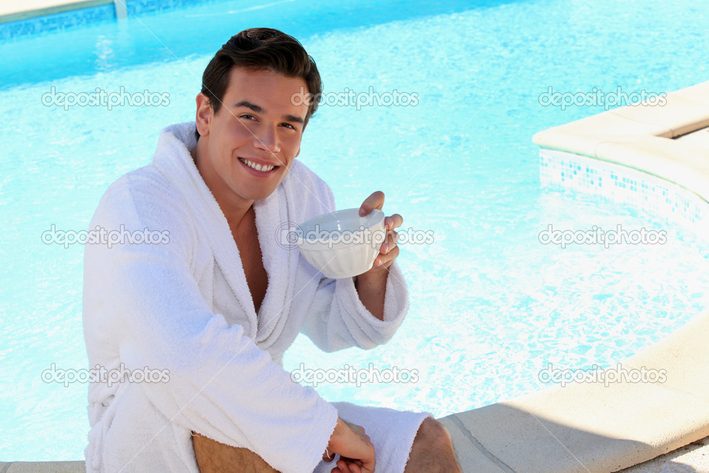 Young man dressed in bathrobe sitting on the edge of a swimming pool and drinking coffee — Stock Photo #7716453