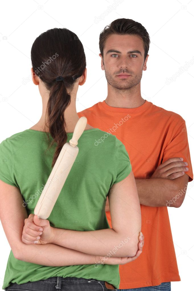 Woman hiding a rolling pin behind her back — Stock Photo #7717100
