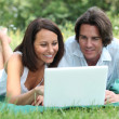 Couple lying on the grass looking at a laptop computer screen — Stock Photo