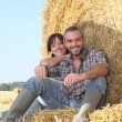 Royalty-Free Stock Photo: Farmer and wife sat on hay bale