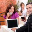 Man using a laptop computer in a cafe with a blank screen for your image — Stock Photo
