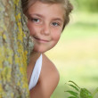 Young girl in white dress hiding behind a tree — Stock Photo #7733437
