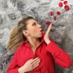 Woman blowing rose petals — Stock Photo #7733987
