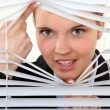 Young woman behind blinds — Stock Photo