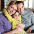 Young family sat on couch — Stock Photo