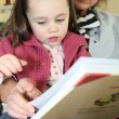 Little girl reading a book with her grandma - Stock Photo