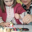 Woman painting with a young girl - Stockfoto