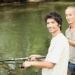 An old man and a young man angling beside a river — Stockfoto #7738565