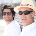 Baba ve oğul güneşli bir günde bir bankta birlikte oturan — Stok fotoğraf