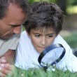 Father and kid with magnifying glass — Stock Photo
