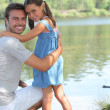 Stock Photo: Father and daughter standing on a riverbank