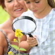 Girl and grandmother with magnifying glass — Stock Photo
