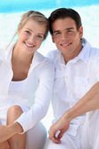 Young couple wearing white with a blue sky background — Stock Photo