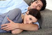 Couple lying on sofa — Stock Photo