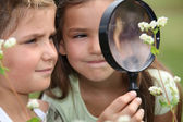 Children with a magnifying glass — Stok fotoğraf