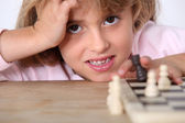 Little girl playing chess alone — Stock Photo