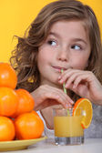 Little girl with oranges and a glass of juice — Stock Photo