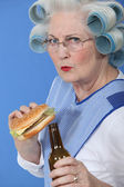 Senior with curlers in her hair drinking beer and eating hamburger — Stock Photo