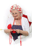 Elderly woman wearing hair rollers whilst knitting — Stock Photo