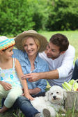 Family with small white dog — Stock Photo