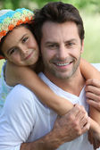 Girl on father's back — Stock Photo