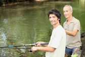 An old man and a young man angling beside a river — Stock Photo