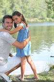 Father and daughter standing on a riverbank — Stock Photo