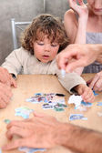 Little boy playing with pictures at a table — Stock Photo