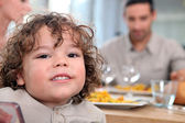 Young girl having a meal with her family — Stock Photo