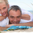 Couple laid together on beach — Stock Photo