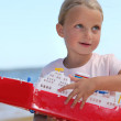 Girl holding toy ship — Stock Photo #7740082
