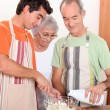 Stock Photo: 20 years old boy and 65 years old mand wommaking cake together