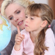 Mother and daughter looking at a globe light — Stock Photo #7740547