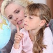 Mother and daughter looking at a globe light — Stock Photo