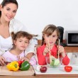 Stock Photo: Mother and daughters preparing salad