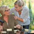A young blonde woman touching shoulders of an old blonde woman taking a cru — Stock Photo